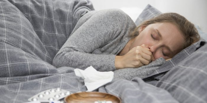 Sick young fair-haired Caucasian woman covered with plaid lying in bed with closed eyes, coughing, closing mouth with napkin. Pills on tray on bed. Illness, pain concept
